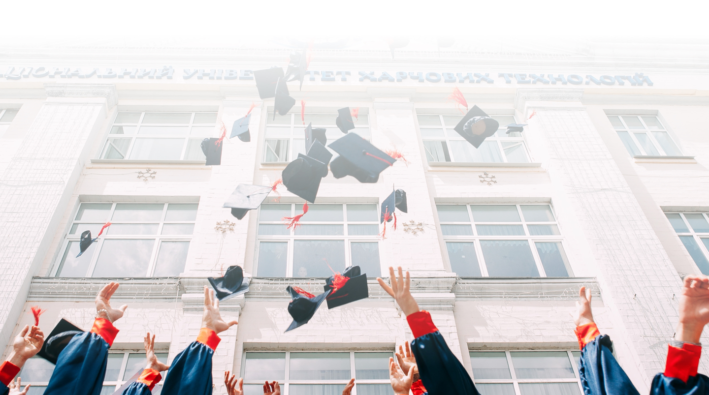 A group of students throwing graduation caps in air