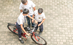 Student of SIS riding a push cycle